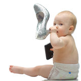 Toddler in diaper playing with shoe and phone Royalty Free Stock Image
