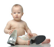 Toddler in diaper playing with shoes Stock Photo