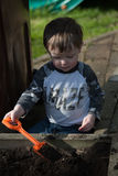 Toddler digging soil. A toddler playing in the garden, digging soil with a trowel stock photography