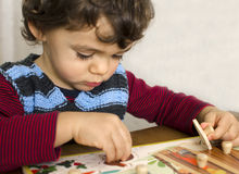 Toddler doing a puzzle. Toddler doing first puzzle to learn shapes colors. Educational concept royalty free stock photography