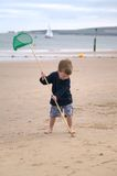 Toddler doing a sand drawing. Royalty Free Stock Images