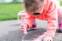 Street charlk art. Toddler drawing with chalk on paved walk near playground Stock Images