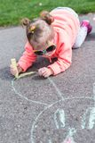 Street charlk art. Toddler drawing with chalk on paved walk near playground Royalty Free Stock Photo