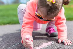 Street charlk art. Toddler drawing with chalk on paved walk near playground Royalty Free Stock Image