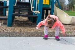 Street charlk art. Toddler drawing with chalk on paved walk near playground Stock Photos