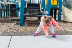 Street charlk art. Toddler drawing with chalk on paved walk near playground Stock Photography