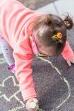Street charlk art. Toddler drawing with chalk on paved walk near playground Stock Photo