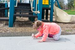Street charlk art. Toddler drawing with chalk on paved walk near playground Royalty Free Stock Photography