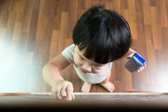 Toddler drawing on chalkboard. Little Asian child concentrate on drawing at the chalkboard Stock Photo
