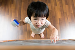 Toddler drawing on chalkboard. Little Asian child concentrate on drawing at the chalkboard Royalty Free Stock Photos