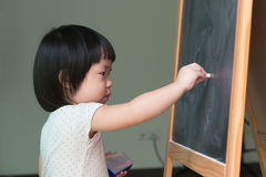 Toddler drawing on chalkboard. Little Asian child concentrate on drawing at the chalkboard Stock Images