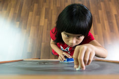 Toddler drawing on chalkboard. Little Asian child concentrate on drawing at the chalkboard Royalty Free Stock Photo