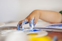 Toddler drawing with colored water color with fingers on a table royalty free stock photo