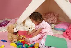 Toddler Drawing and Playing at Home. Toddler girl playing and drawing at home: indoor pretend play Royalty Free Stock Photo