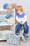 Toddler dreaming about Christmas. Cute little kid sitting on a white wooden chair next to the shelf with teddy bears and gift boxes and dreaming about Christmas Stock Photography