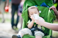 Toddler drinking water stitting in pram outdoors royalty free stock photos