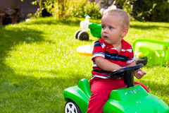 Toddler driving toy car outdoors. Toddler driving toy car in the garden Royalty Free Stock Images