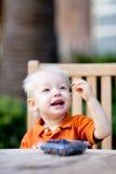 Toddler eating berries Royalty Free Stock Image
