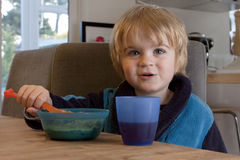 Toddler eating breakfast Stock Images