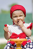 Toddler eating a cherry. Cute toddler eating an sweet cherry stock images