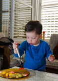 Toddler eating with a fork Royalty Free Stock Photos