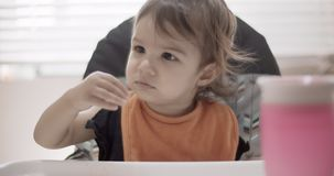 Toddler eating her dinner. Slow motion. Shot in 4K RAW on a cinema camera stock video footage