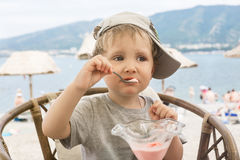Toddler eating ice cream in a cafe on the beach Stock Photo