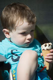 Toddler eating ice cream. A toddler sitting and enjoying an ice cream cone royalty free stock images