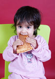 Toddler eating pizza slice Stock Images