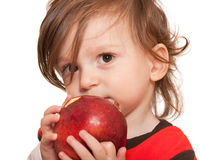 Toddler eating a red apple Stock Photo