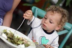 Toddler eating salad stock photos