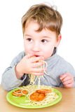 Toddler eating spaghetti with fingers Stock Images