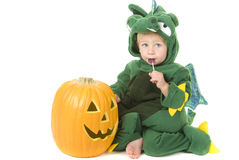 Toddler eats lollipop while wearing dragon costume Stock Images