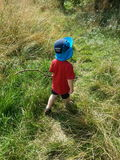 Toddler explorer. Walking with stick in the great outdoors Stock Photos