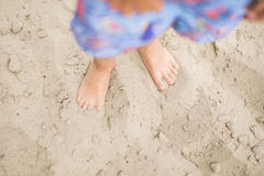 Toddler feet on sand at the beach. Child in blue shorts walking barefoot. Having fun at summertime Stock Images