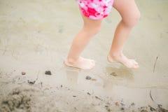 Toddler feet in water at the beach. Child in pink shorts walking barefoot in transparent lake water. Having fun at summertime Stock Image