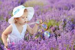 Toddler in field with bubbles Stock Photo