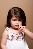 Toddler with finger in nose. Cute mischievous toddler girl with finger in her nose fishing for boogers snot, on brown Royalty Free Stock Photos