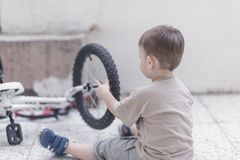 Toddler fixing a bicycle Royalty Free Stock Images
