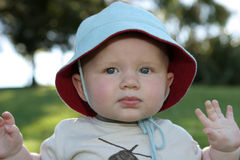 Toddler in floppy sun hat. Portrait of toddler in floppy sun hat outdoors royalty free stock photos
