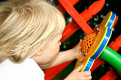 Toddler with flower speaker. '' Hello Mummy ! ''. Girl toddler shouting into a playground flower shaped speaker in fun colors Stock Photo