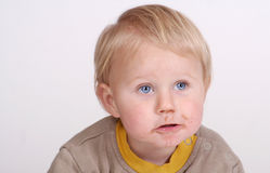 Toddler with food around mouth. A portrait of a young toddler seen here is a studio picture on a white background. He has food around his mouth after he has been royalty free stock photo