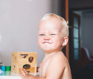 Toddler frowns and expresses disagreement on his face. Cute toddler frowns and expresses disagreement on his face. Adorable baby boy makes a funny serious stock photo