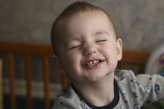 Toddler with Funny Expression. Two year old male toddler in his crib making a funny face.  The toddler is showing his teeth and wearing pajamas Royalty Free Stock Image