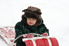 Toddler with furry hat on toboggan Royalty Free Stock Photo