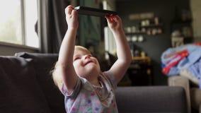 Toddler garota assiste filme no smartphone vídeos de arquivo