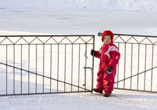 Toddler at the gate. Small child standing by an open gate, a cold and snowy winter day Royalty Free Stock Image