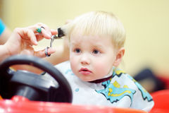 Toddler getting his first haircut. Sweet toddler child getting his first haircut Stock Photos