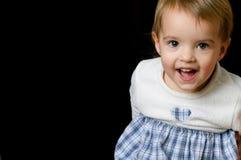 Toddler girl. Smiling toddler girl in white & blue on black background Stock Photos