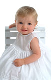 Toddler girl. Sitting on chair sideways, smiling, in white dress, on white background stock photo